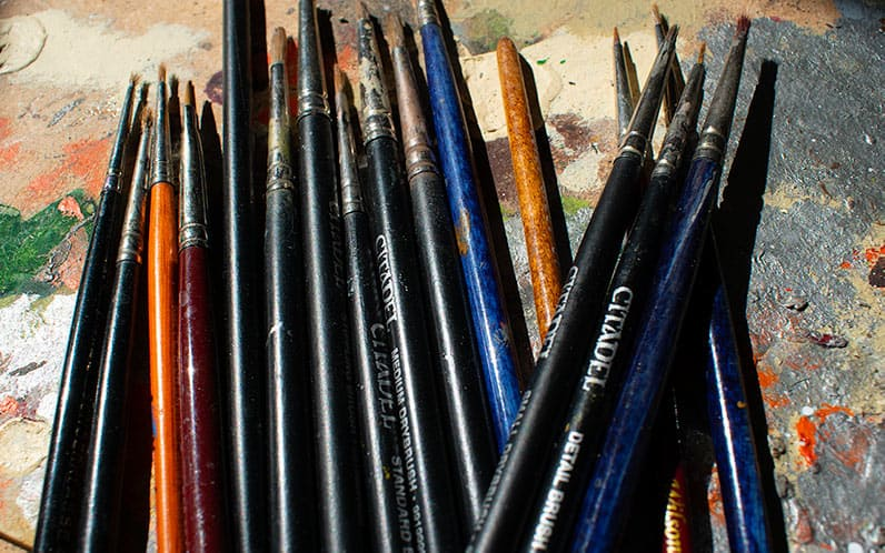 A picture of a bunch of different (and some of them broken) brushes for miniature painting