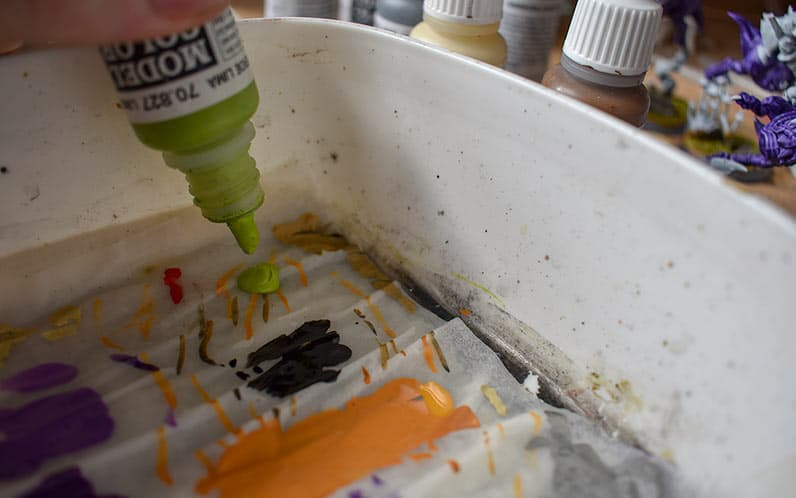 A picture showing a vallejo green dropping a drop of paint onto the palette