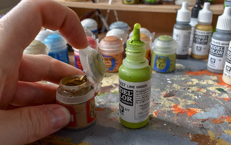An image of vallejo dropper bottle side by side with a citadel paint pot showing the dryed paint in the lid