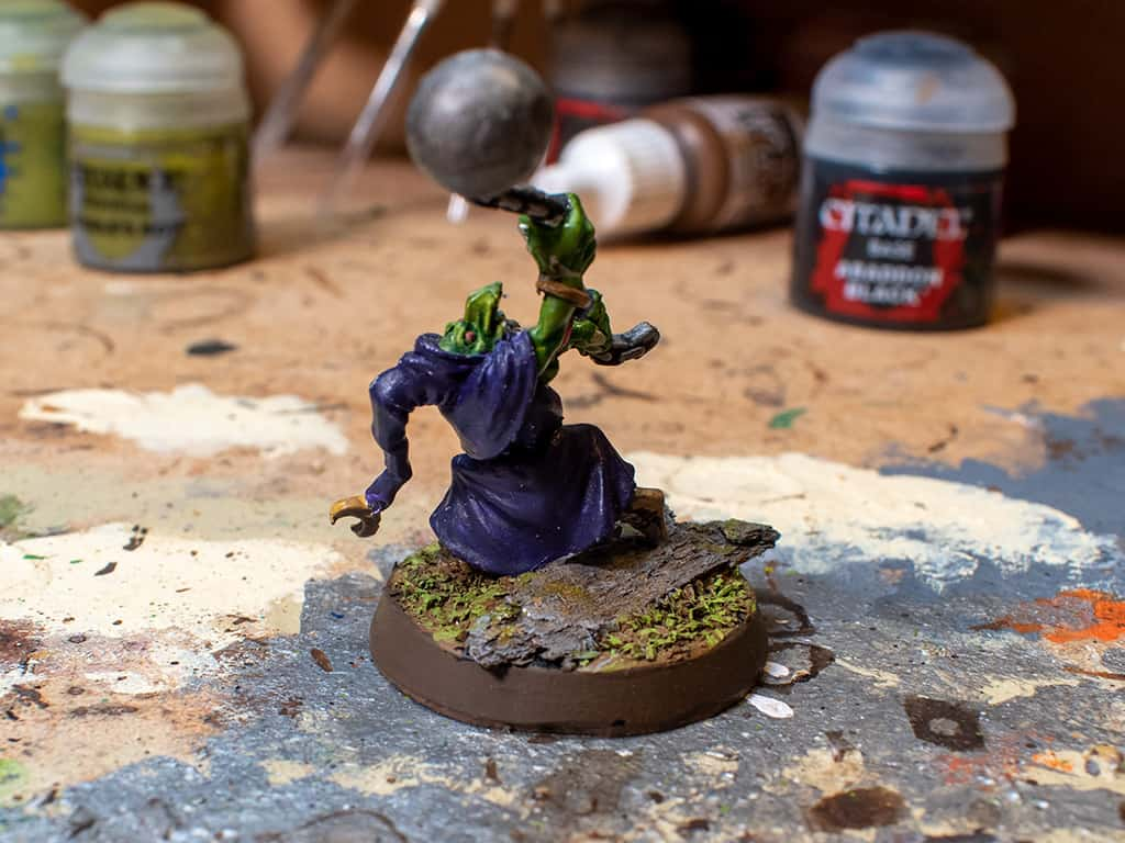 A gloomspite Git painted with a purple robe, but the basecoat was too thick when applied