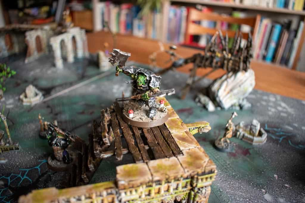 In Ironjawz Brute with black armour standing on a platform of some warcry terrain
